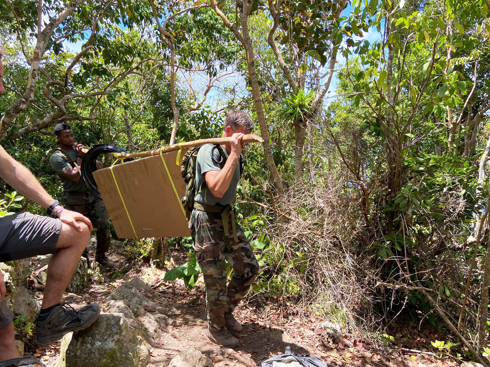 SGIS Defense personnel carrying material on North Coast trail