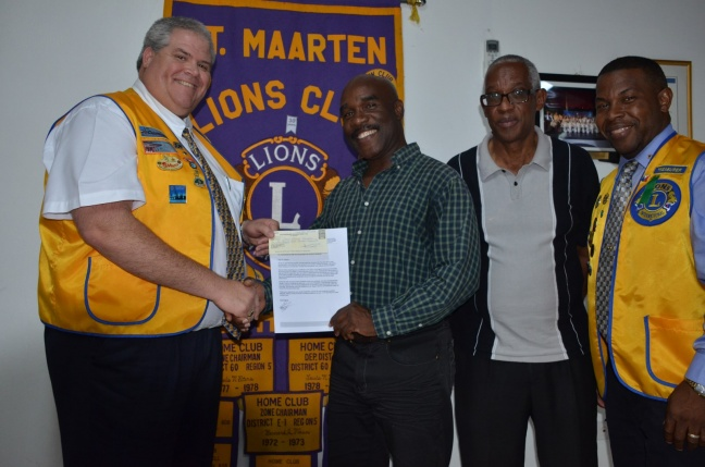 The St. Maarten Lions Club President Lion Claudio Buncamper hands over the donation check to Sir Isidore York in the presence of the St. Maarten Lions Club Treasurer Lion Alphons Gumbs and another member of Dow's Foundation