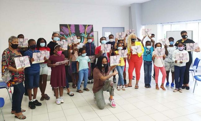 St. Martin children with copies of Fela! Let Music Be The Weapon. Visiting US author Iris Wilson (7th R) presented the storybook. Also in photo: Nicole de Weever, ASLF president (R); Nangwaya Gibson, illustrator of Fela! (center, front); and Jacky Vrolijk, SOS radio DJ (L), who accompanied her grandson. Chamber of Commerce building, Marigot, 2.19.21. (CLF photo.)