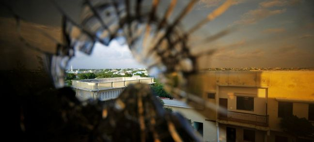 UN Photo/Stuart Price The skyline beyond the northern suburbs of Mogadishu is seen through a bullet hole in the window of a hotel in Somalia.